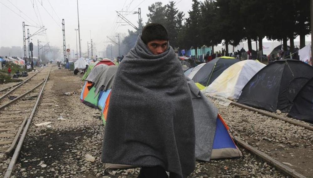 Un joven refugiado cubre su cuerpo con un manta en el campamento provisional de Idomeni, en la frontera entre Grecia y Macedonia (Grecia).