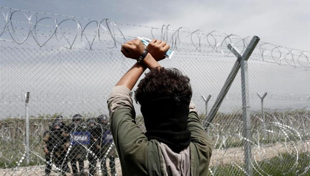 Un refugiado permanece tras la valla fronteriza frente a un grupo de policías macedonios