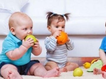 Varios bebés comiendo fruta