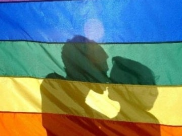 Dos jóvenes se besan tras la bandera LGTB