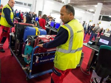 Empleados del aeropuerto cargan con el equipaje en el aeropuerto de Zaventem, cerca de Bruselas.