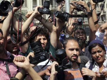 Periodistas alzan sus cámaras en señal de protesta durante una manifestación en El Cairo