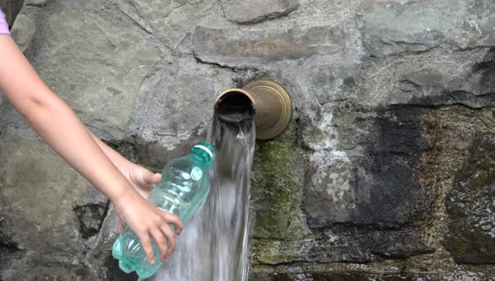 Imagen de una persona llenando una botella de agua