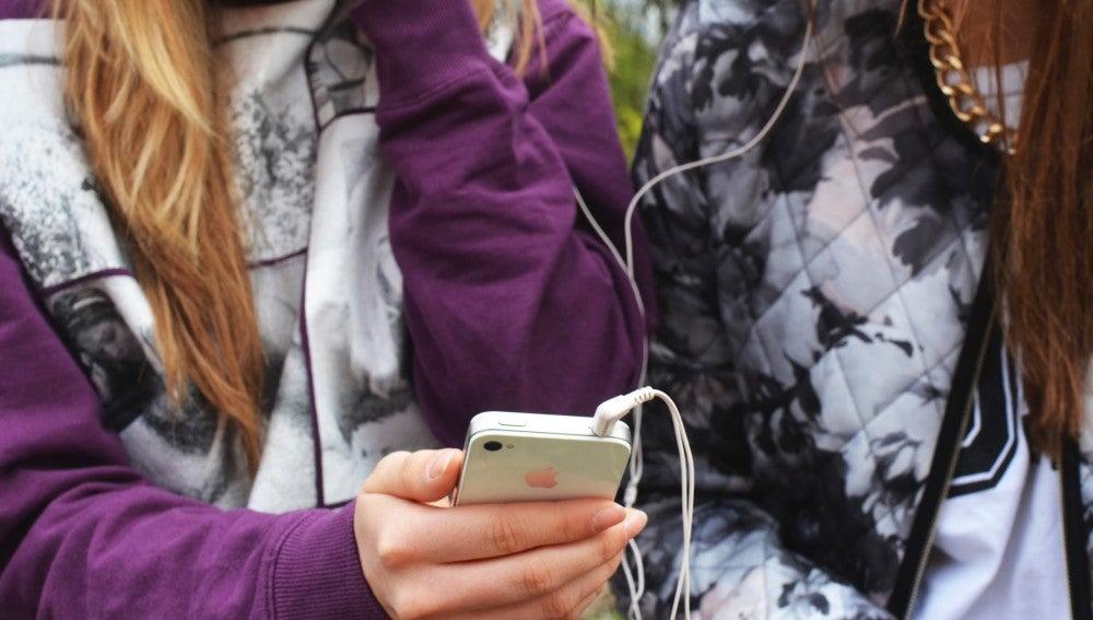 Unas jóvenes con un teléfono móvil