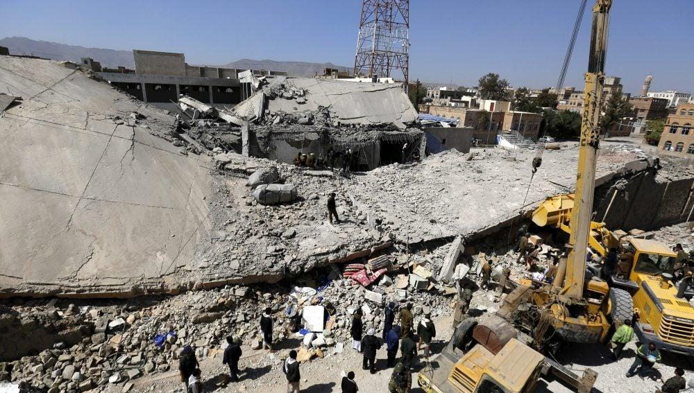 Un grupo de personas inspeccion los restos de la sede principal de la Policía tras un bombardeo en Yemen