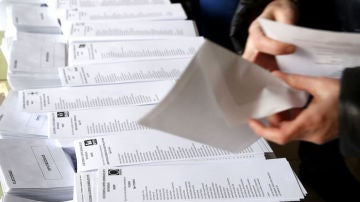 Una persona introduce una papeleta electoral en un sobre.
