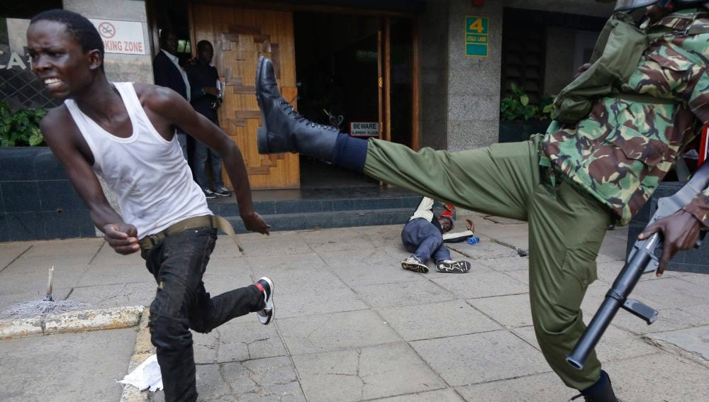 Un hombre corre para evitar ser golpeado por un agente de policía