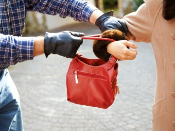 Un ladrón robando un bolso