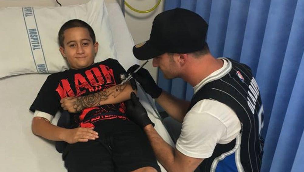 Imagen del tatuador australiano, con uno de los niños