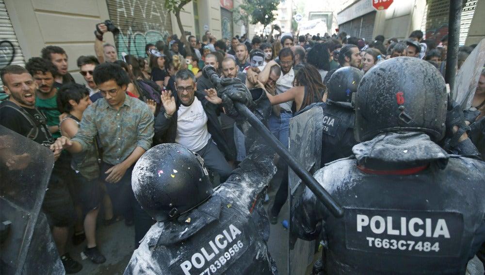 Manifestantes y antidisturbios de los Mossos d'Esquadra, durante los incidentes producidos  en el barrio de Gràcia