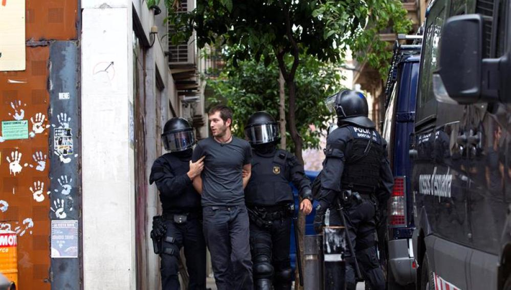Los Mossos d'Esquadra custodian a uno de los okupas detenidos