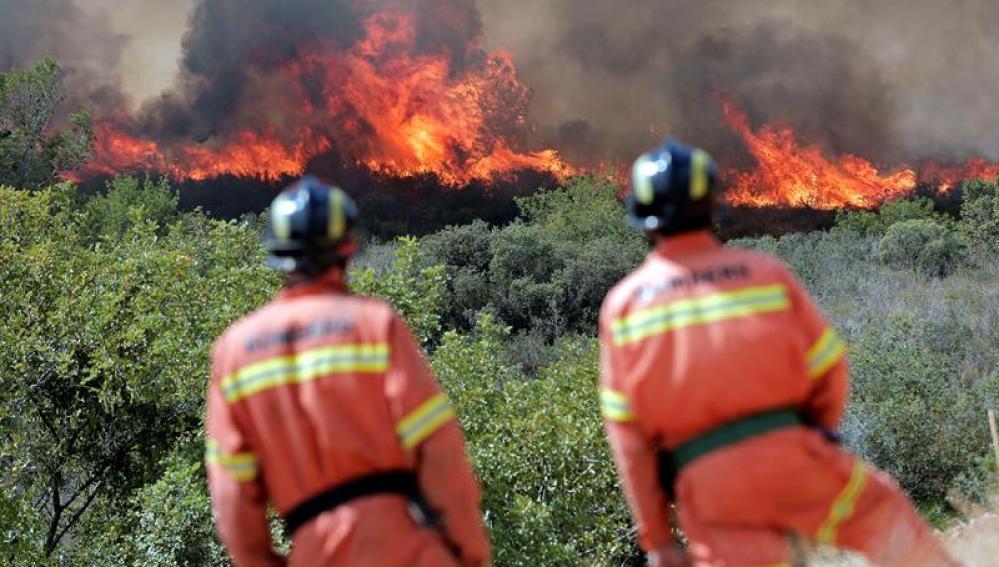 Dos bomberos observan las llamas cerca de la localidad de Sumacarcer (Valencia)