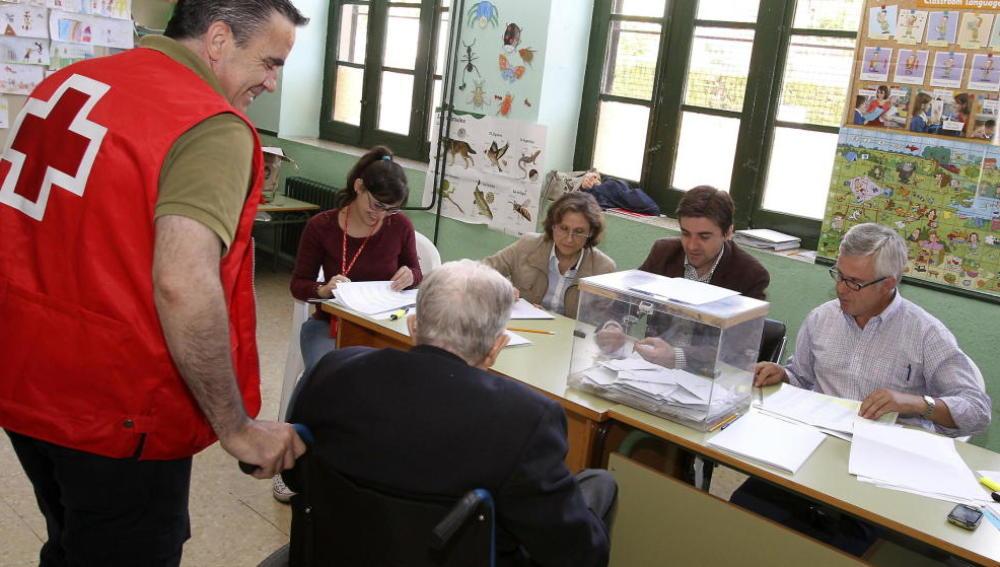 Voluntario de Cruz Roja ayuda a una mujer a depositar su voto