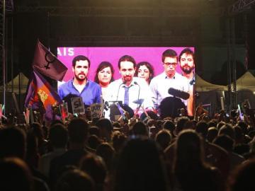 Simpatizantes de Unidos Podemos escuchan las declaraciones de su líder Pablo Iglesias