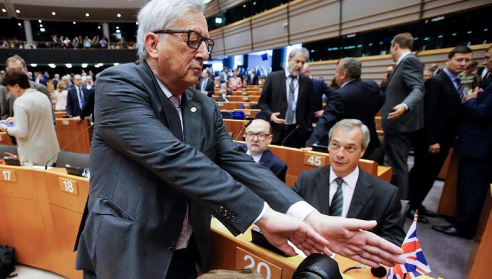 Juncker, intenta tapar la cámara a un fotógrafo que enfoca a Farage
