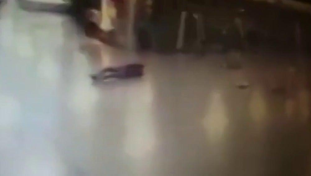 Frame 13.076645 de: Un policía dispara contra uno de los terroristas del aeropuerto de Estambul y huye justo antes de que este se inmole