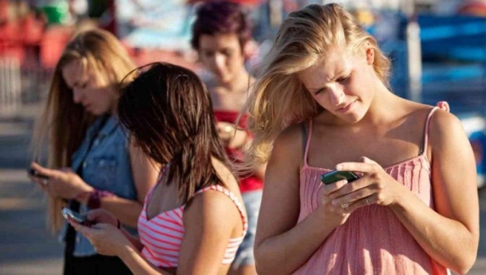 Un grupo de chicas consulta su teléfono móvil