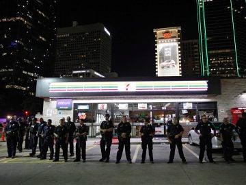 Agentes de la policía de Dallas permanecen en guardia en la esquina de Ross Avenue con Griffin Street durante una manifestación contra la violencia policial hacia los negros en EEUU