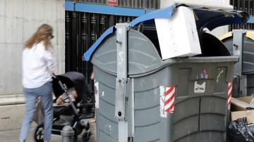 Una madre con su bebé pasa junto a un contenedor