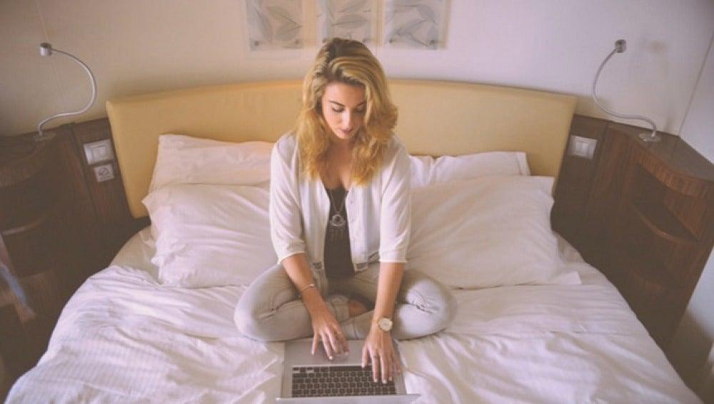 Una chica en la cama con un portátil