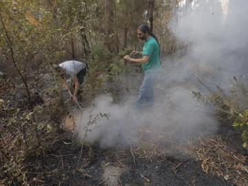 Dos vecinos intentan sofocar un foco del incendio que afecta al municipio coruñés de Porto Do San