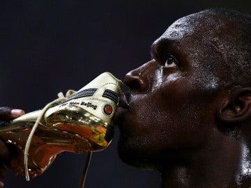 Usain Bolt besa una de sus zapatillas tras la carrera de los 100 metros de los Juegos de Pekín