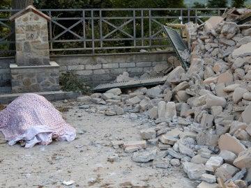 Un cuerpo cubierto con una manta junto a los escombros