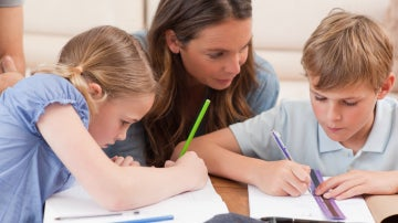 Una madre ayudando a sus hijos con los deberes