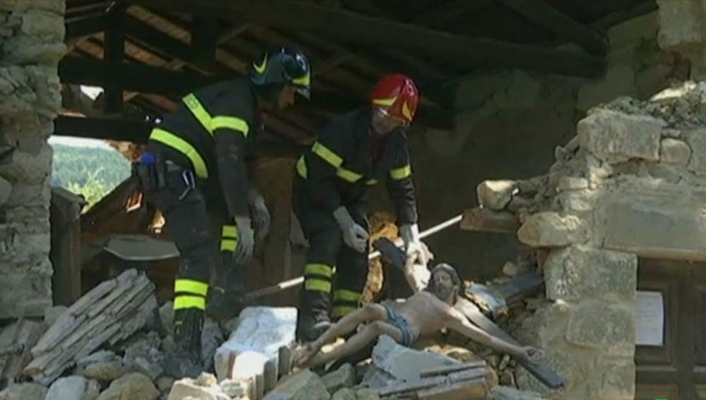 Dos bomberos sujetan una imagen de un cristo en Italia