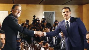 El jefe del Gobierno, Mariano Rajoy y el líder de Ciudadanos, Albert Rivera, se estrechan la mano durante la reunión de sus respectivas delegaciones en la que van a certificar el acuerdo de investidura