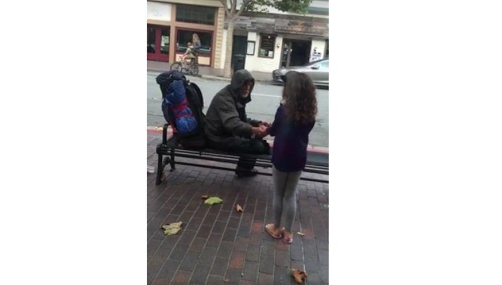Una niña comparte su comida con un vagabundo.