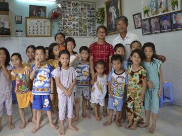 Tong Phuoc Phuc posa junto a varios de los niños que cuida