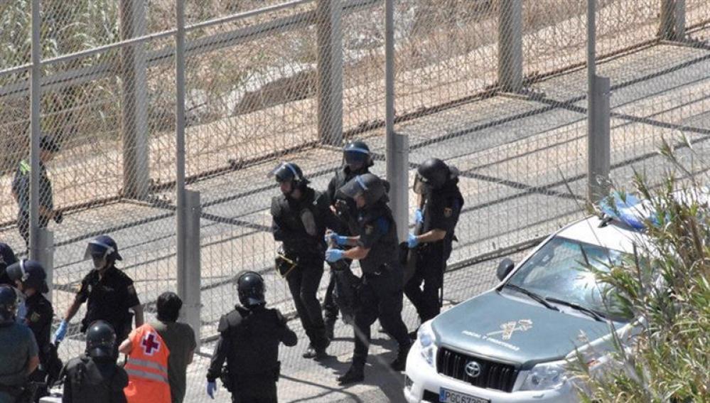 Varios agentes trasladan a un inmigrante en Ceuta