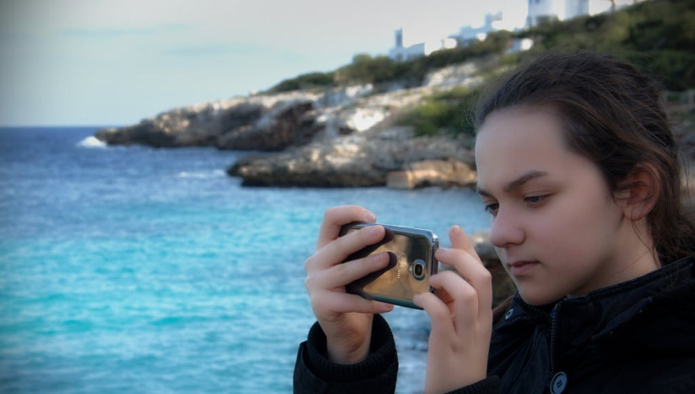 Una adolescente con su móvil