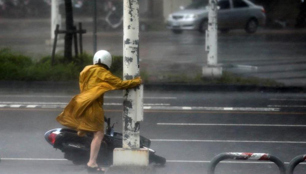 Una motorista se agarra a un poste para evitar ser arrastrada por las fuertes rachas de viento provocadas por el supertifón Meranto