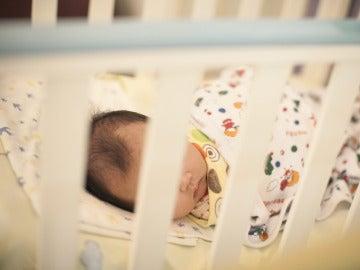 Un bebé duerme en una cuna