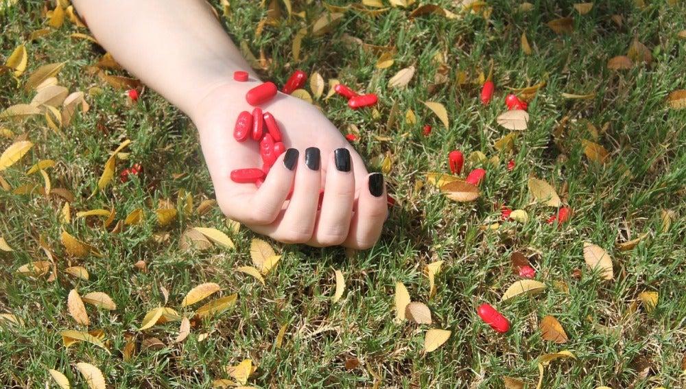 Pastillas caen de la mano de una joven