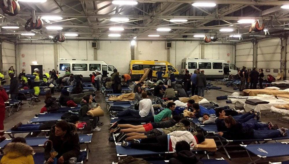 Personas evacuadas por los terremotos, pasan la noche en un hangar de autobuses convertido en refugio temporal, en Camerino, Italia