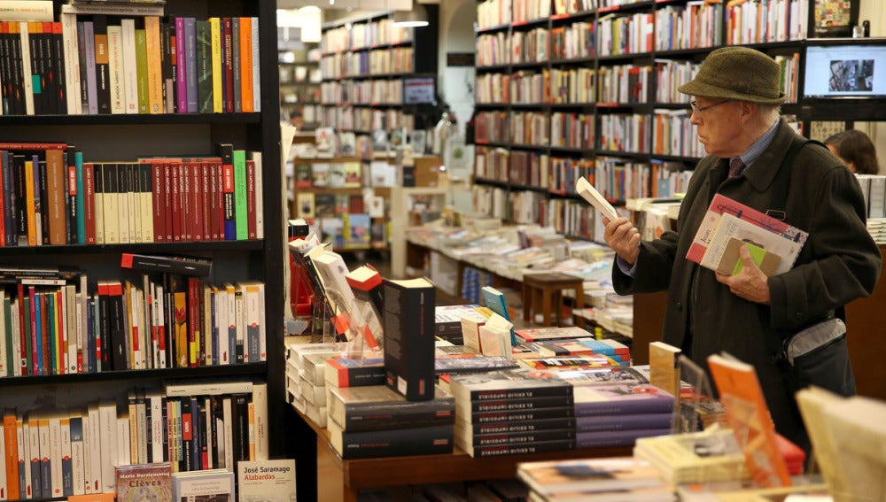 Un hombre mira un libro en una librería