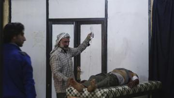 Un sirio atiende a un herido por los bombardeos en Alepo