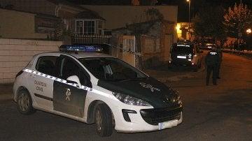 Un coche de la Guardia Civil junto a la vivienda donde se encontraron los cuerpos