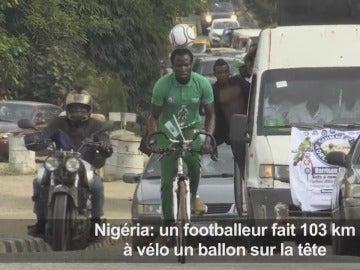 Harrison Chinedu montado en bici con el balón en la cabeza