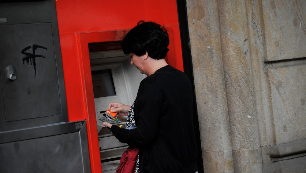 Una mujer saca dinero de un cajero automático