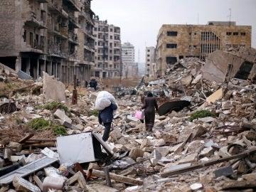 Varios sirios caminan sobre las ruinas de Alepo