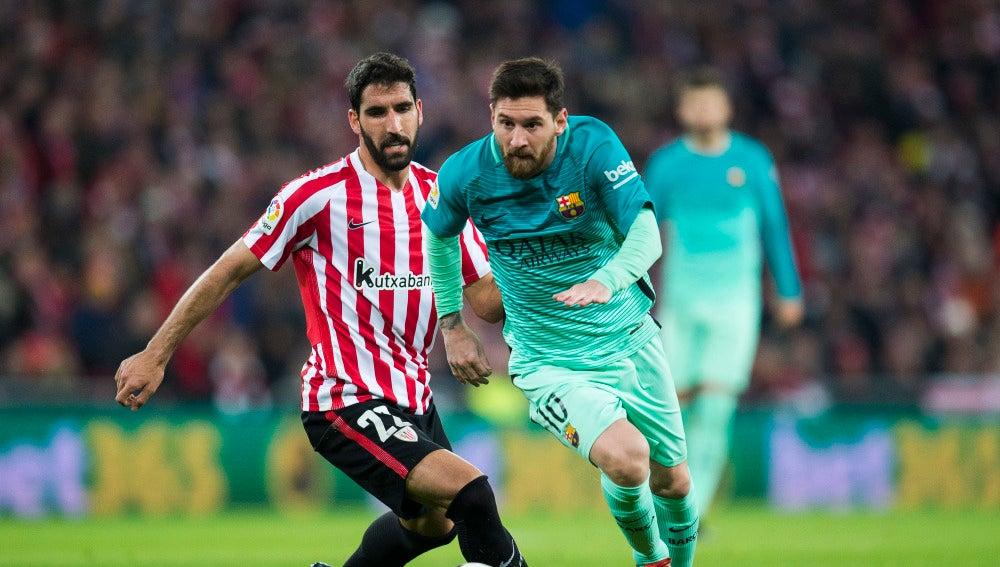Messi conduce el balón mientras Raúl García intenta robárselo