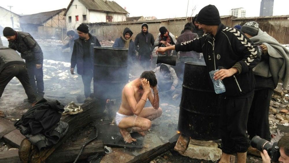 Un refugiado ayuda a otro a asearse en las gélidas calles de Belgrado