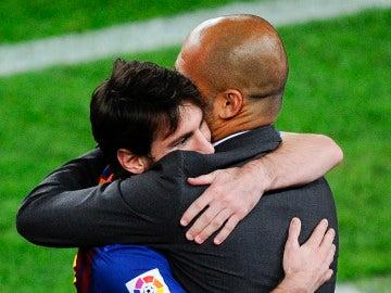 Leo Messi y Pep Guardiola se abrazan durante un partido