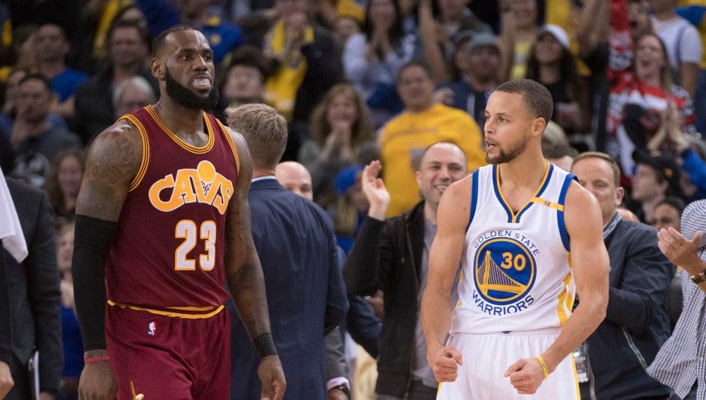 Stephen Curry celebra una canasta ante la mirada de LeBron James