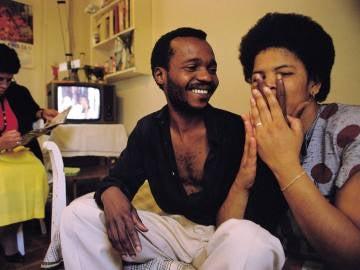 Una pareja de inmigrantes sonríe en su salón