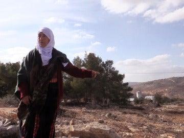 Una anciana palestina señala las tierras de su propiedad, sobre las que se asienta la colonia de Amoná
